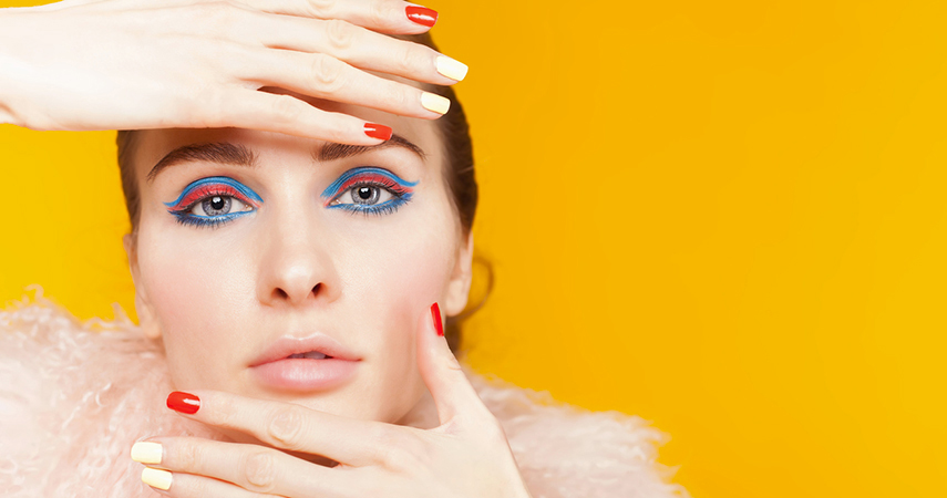 Experiment with eyeliner styles, like this woman's bright blue and pink eyeliner.