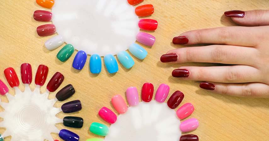 Woman choosing which color of fake nails to apply at the salon.