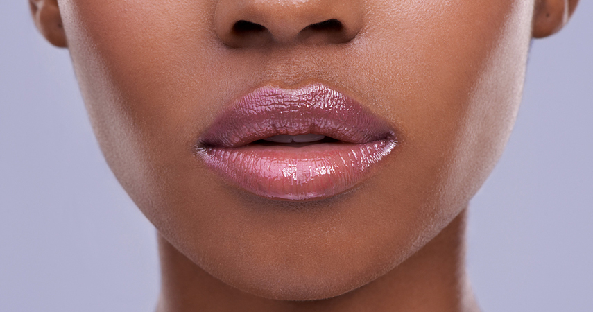 Black woman wearing a neutral pink-brown lip gloss to accentuate her lips.