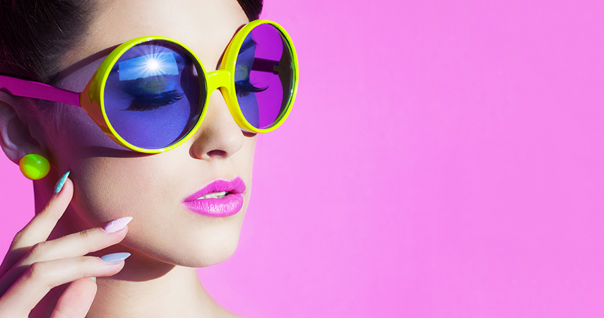 Young woman wearing fun sunglasses and purple lip products.