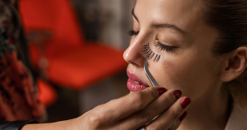 This woman is learning how to apply false eyelashes.