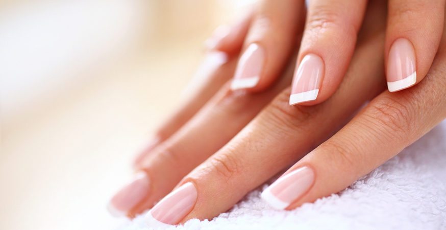Square-shaped fingernails painted with a french manicure.
