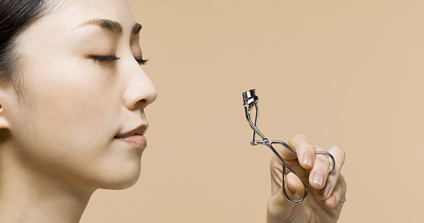 Our tips will help you learn how to use an eyelash curler like this woman