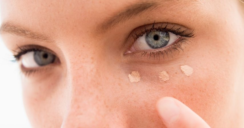 woman applying concealer to show how to cover dark circles