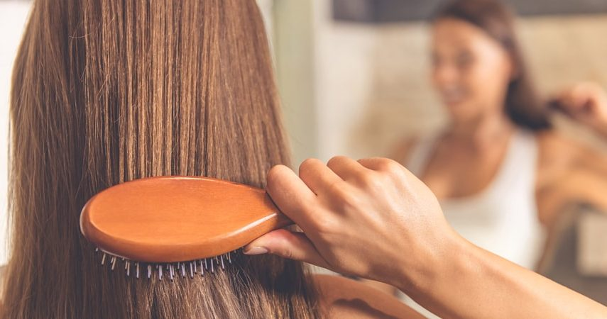 woman brushing hair how to straighten hair without heat