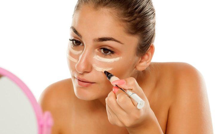 woman applying concealer to dark circles