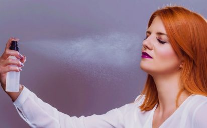 woman using hydrating setting spray for makeup