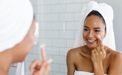 woman applying moisturizer to skin