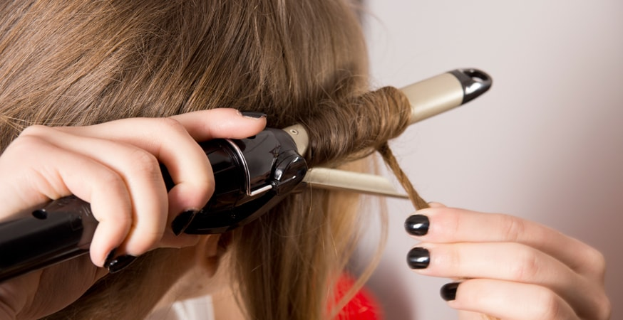 A woman using a curling iron on her hair
