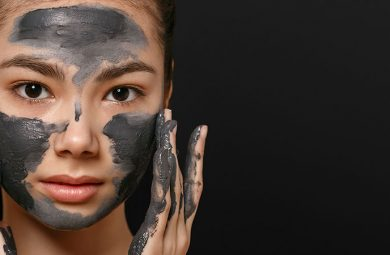A woman is applying a charcoal face mask
