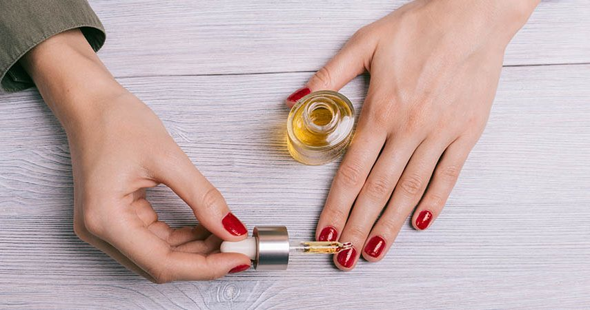 An individual is applying cuticle oil to their nails
