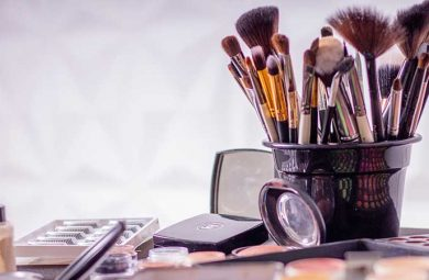 A jar of makeup brushes, and makeup palettes
