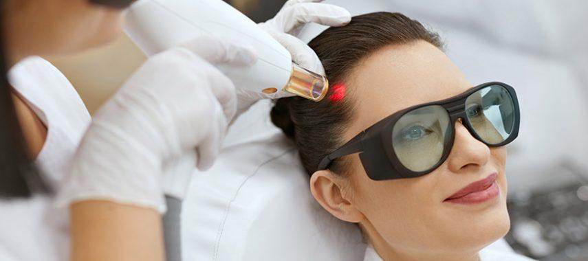 Woman receiving laser hair growth treatment