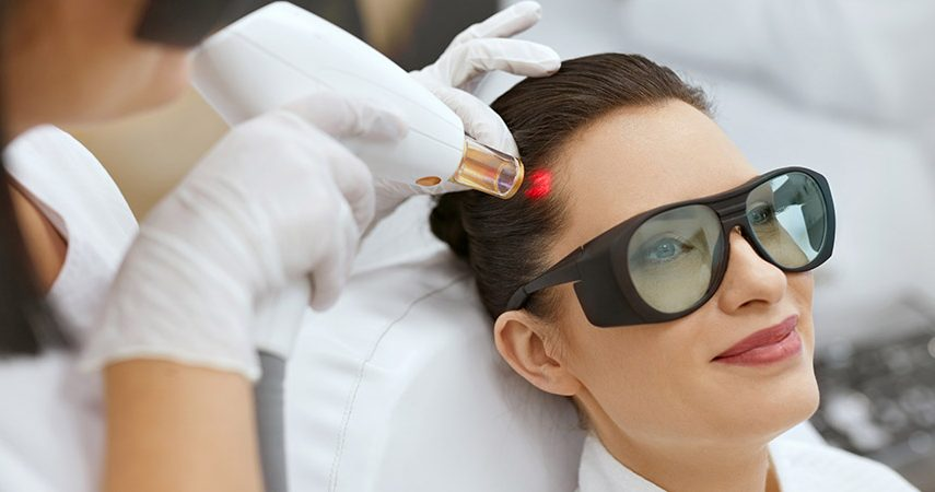 Woman receiving laser hair growth treatment