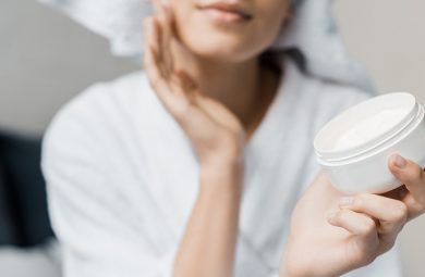 Girl applying cream on face