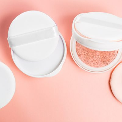 BB cushion on a pink background with sponge and puff