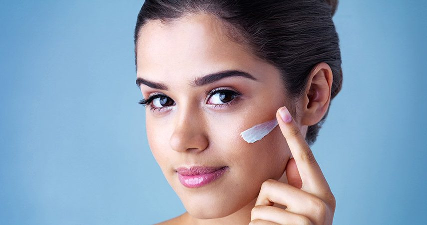 young woman applying face cream against a blue background