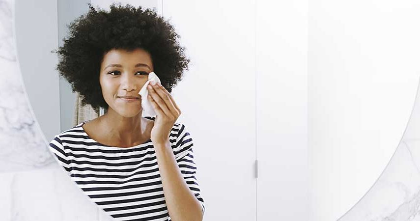 A woman using a face cleaner wipe