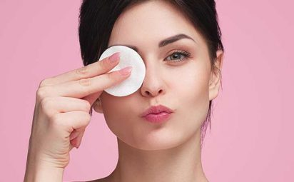 A woman using a cotton pad to remove her makeup