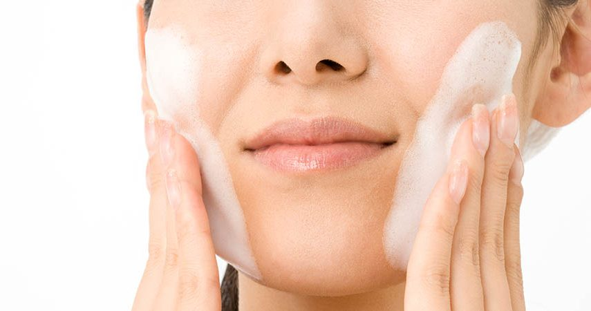 Woman is washing her face with a cleanser