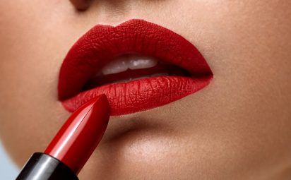 Closeup of woman face with bright red matte lipstick on lips
