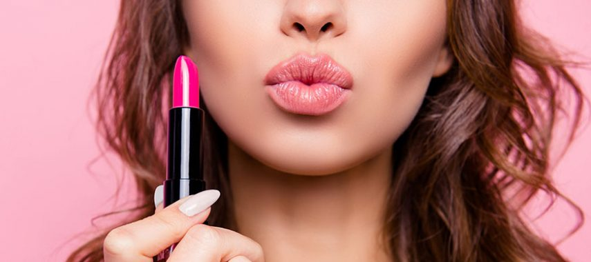 A woman is holding lipstick and puckering her lips