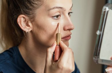 woman applying liquid concealer under eye
