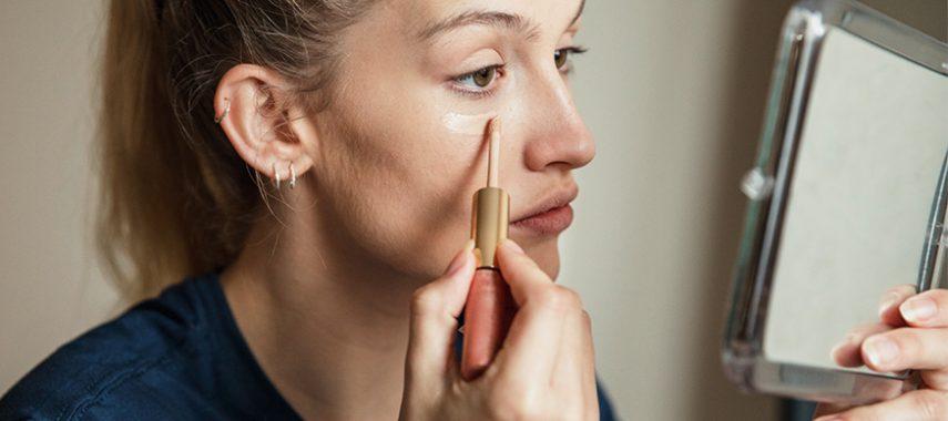 woman applying liquid concealer under eye