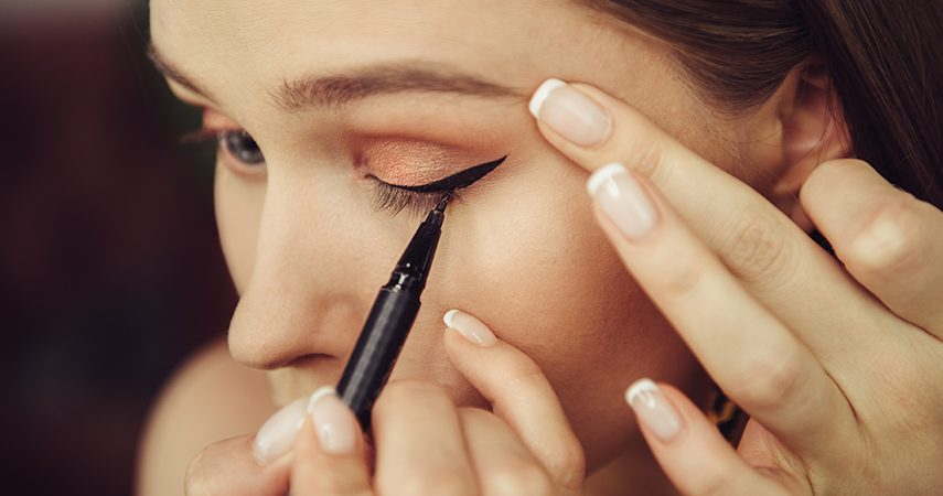 a woman applying black liquid eyeliner