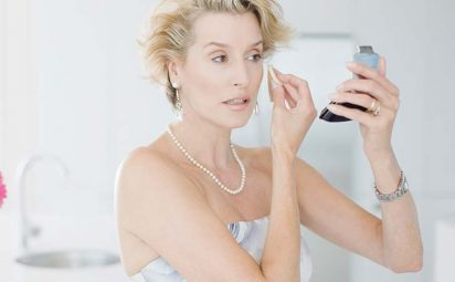mature woman applying makeup with a beauty sponge