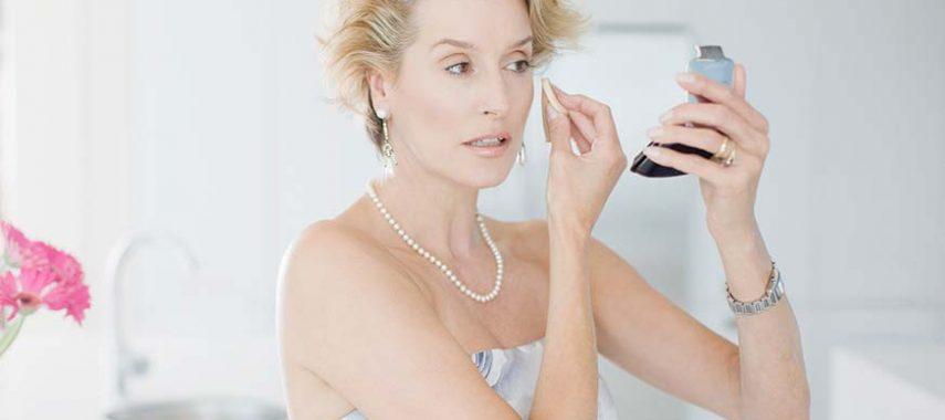 mature woman applying makeup with a beauty sponge