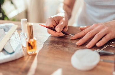 woman fixing cuticles with nail tool