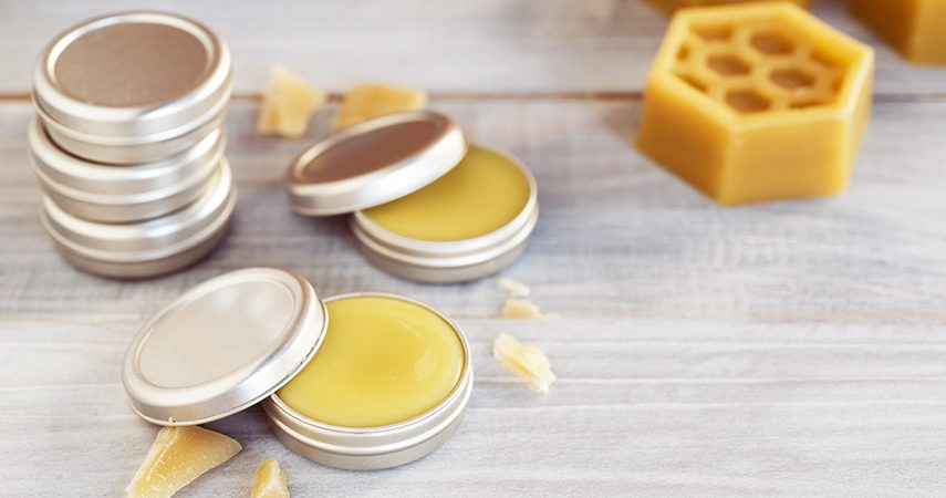 small metal tins filled with beeswax lip balm sit on a wooden surface