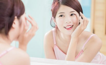 asian woman touching eyelashes while looking in mirror