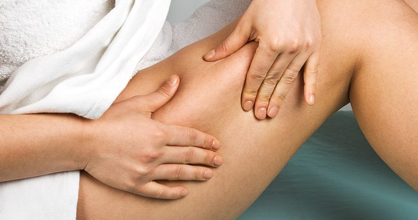 person pinching thigh for cellulite check