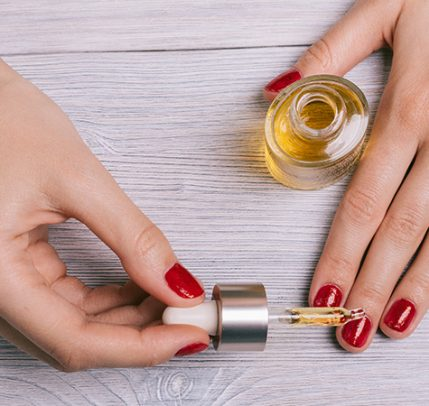 woman with red painted finger nails putting oil on cuticles
