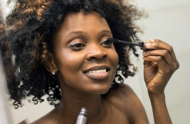 black woman applying mascara in a mirror