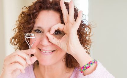 woman using eyelashes curler and mascara with happy face smiling