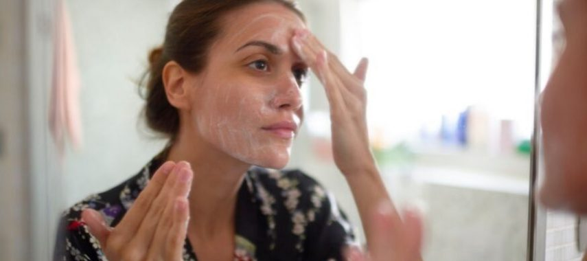 A lady is putting lotion on her face.
