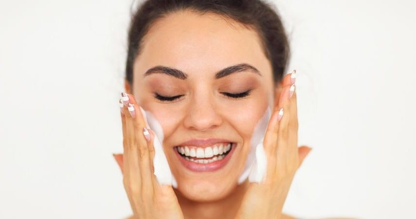 A girl washing her face with a cleanser that is good for sensitive skin.
