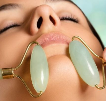 Somone is getting a jade facial roller treatment.