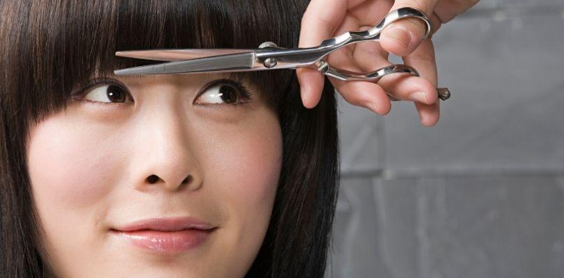 Someone cutting their own bangs.