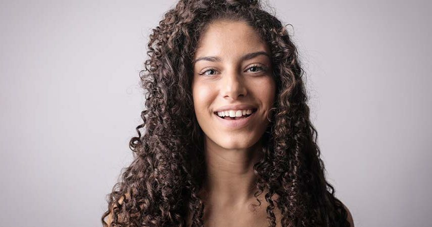 A girl with brown curly hair smiling in front of a brown/grey background.