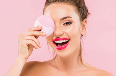 A girl posing with a facial cleansing brush in front of a pink background.