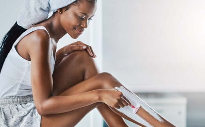 A woman in a bathroom shaving her legs.