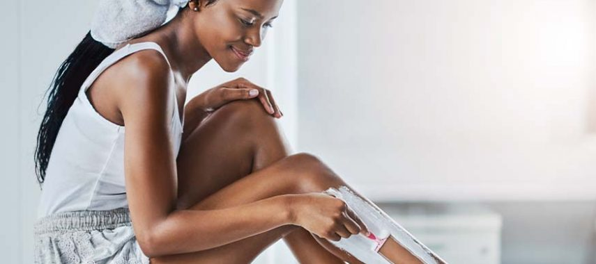 A woman in a bathroom shaving her legs.