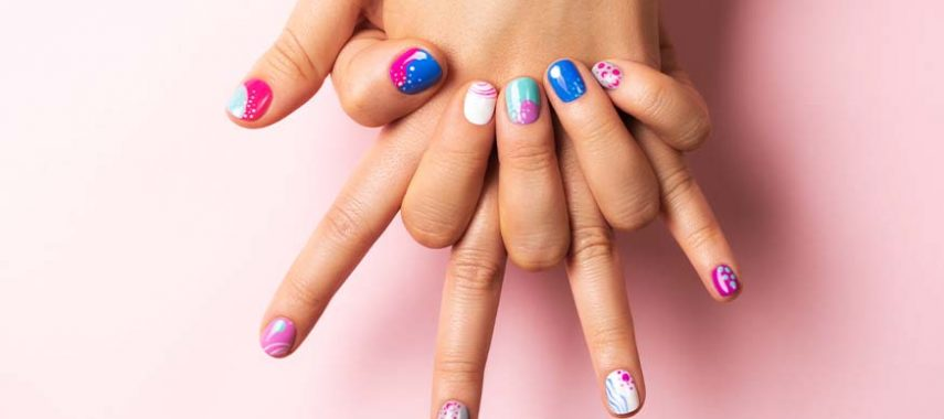 Someone showing summer nail designs against a pink background.