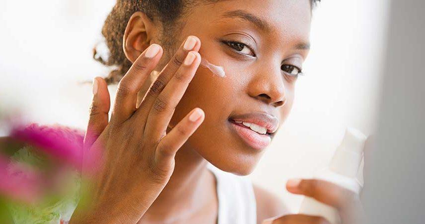 A woman applying SPF sun cream to her face.
