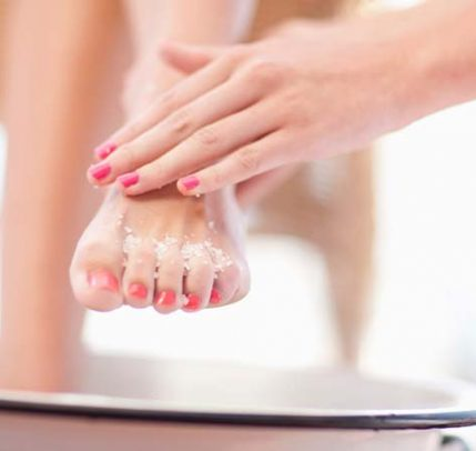 A person holding another person's foot and applying foot scrub.
