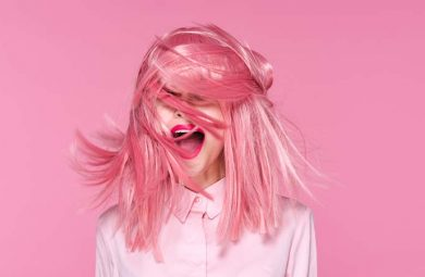 Someone standing in front of a pink background with pink hair.